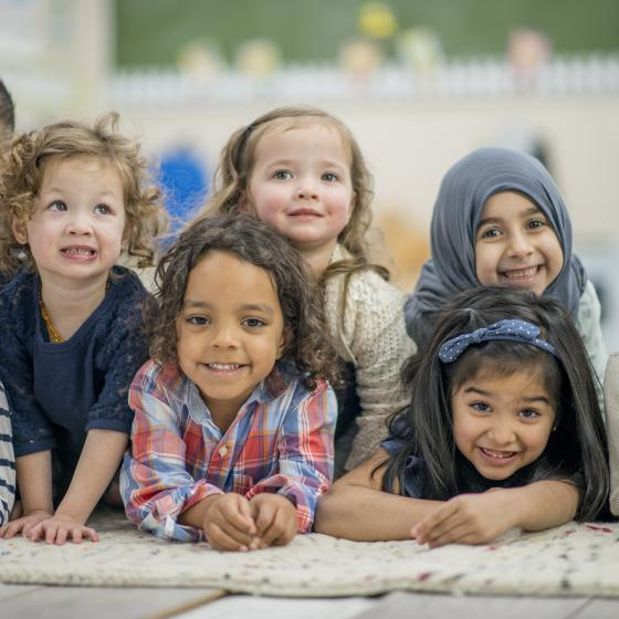 multi-racial pre-school kids gathered on mat