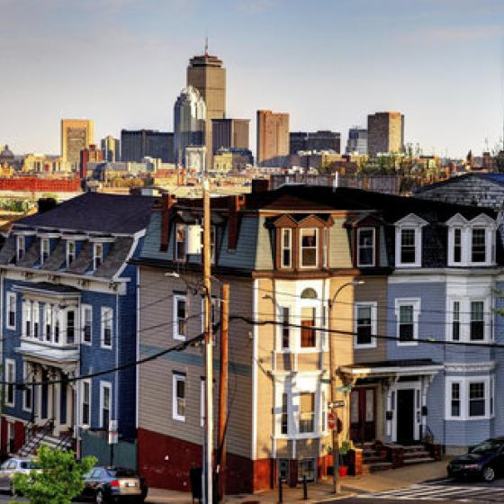 View of crowded Boston row homes with skyscrapers in background